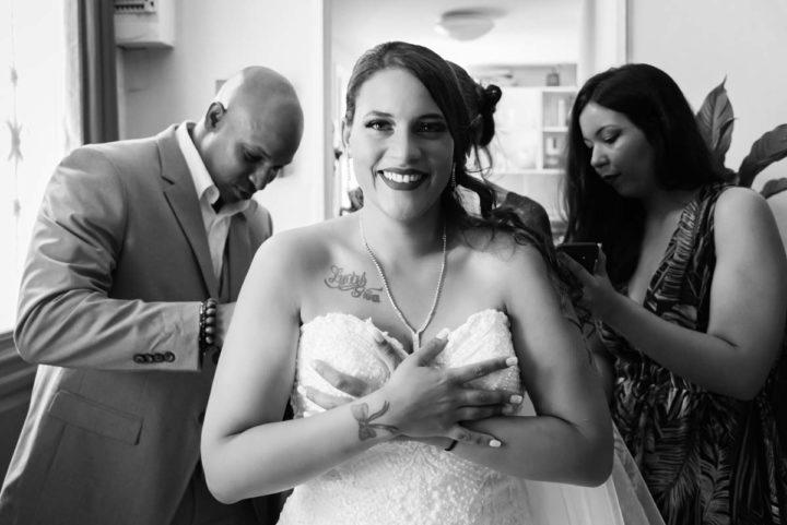 La mariée enfile sa robe avec ces proches