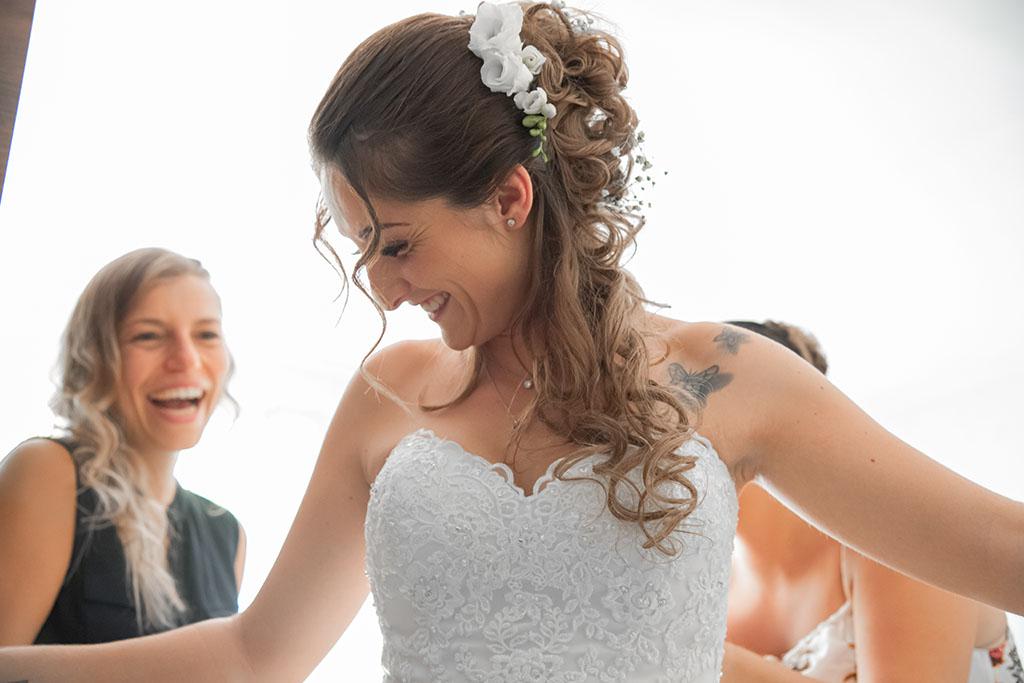 Les préparatif de la mariée dans sa robe avec ses amies et sa famille