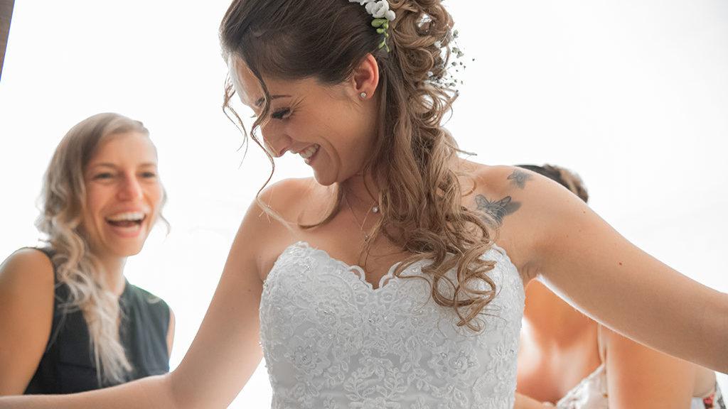 Préparatif de la mariée, elle met sa robe de mariée avec ses amies proches et sa famille