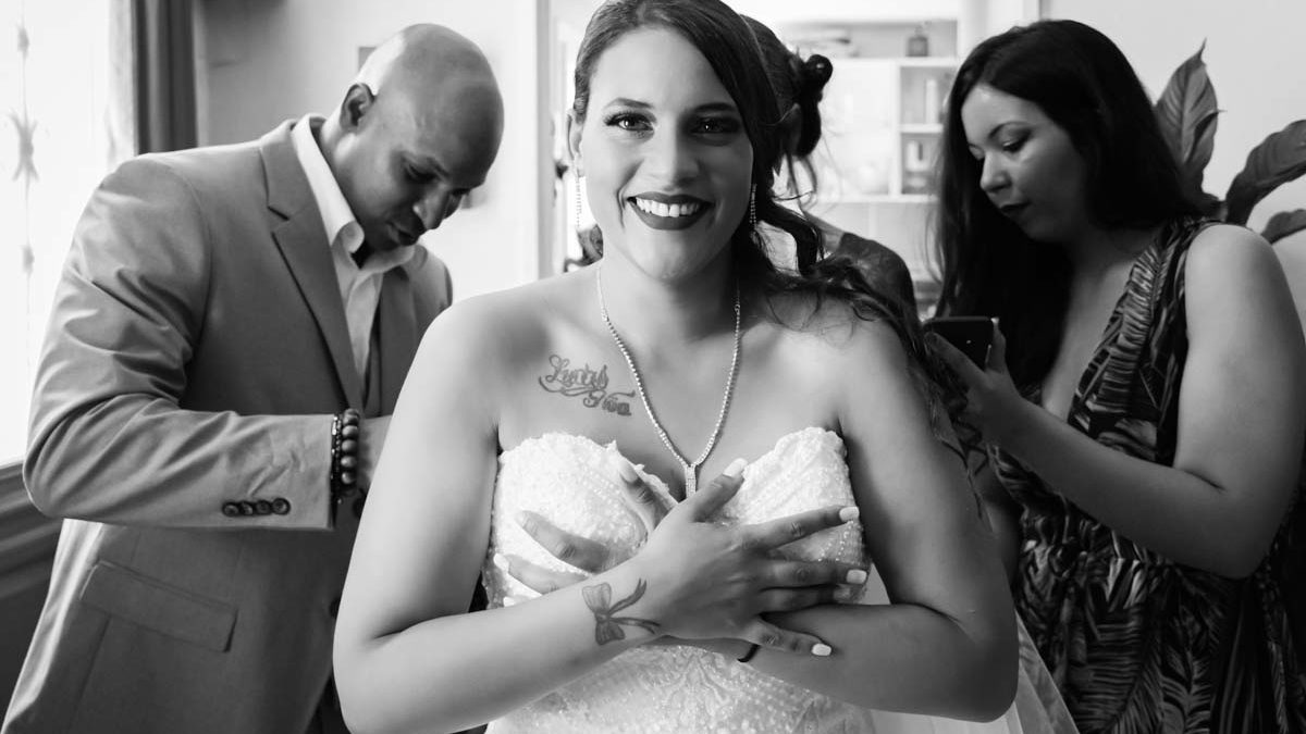 Préparatifs de la mariée qui est en train de mettre sa robe de mariée avec l'aide de ses proches.