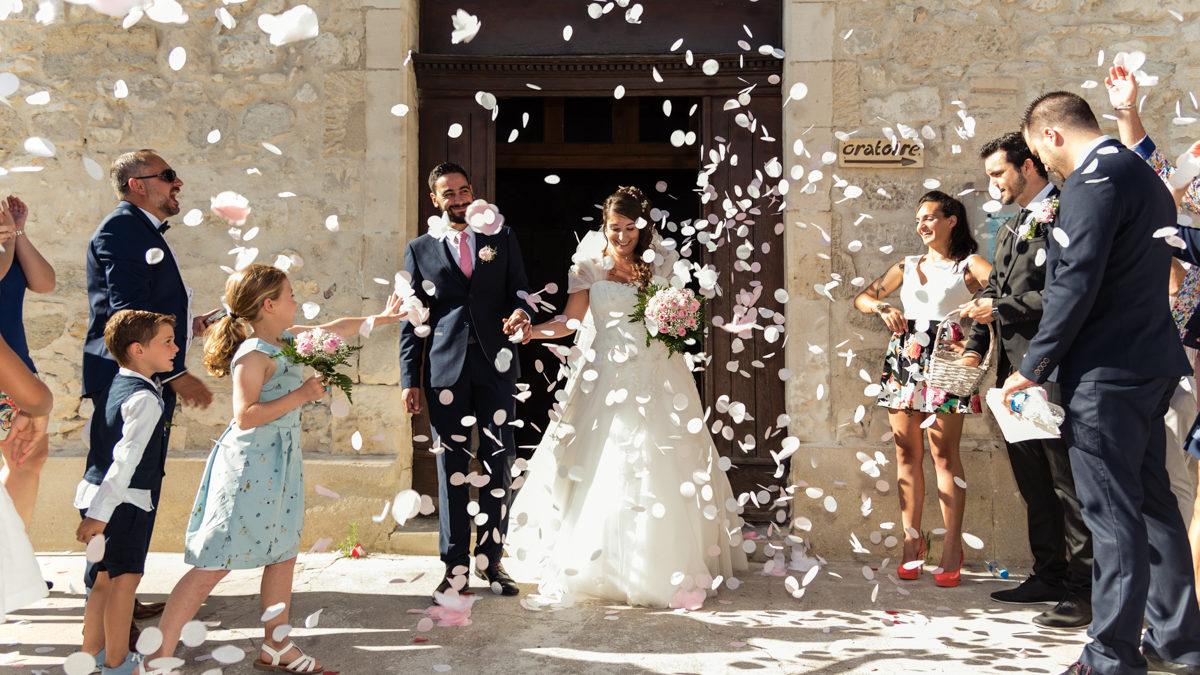Sortie d'église sous les confettis devant les invités avec une robe de mariée et un costume de marié